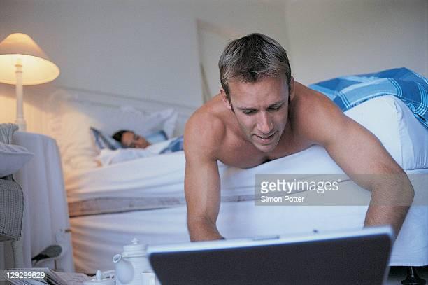 Uomo utilizzando un computer portatile in camera da letto