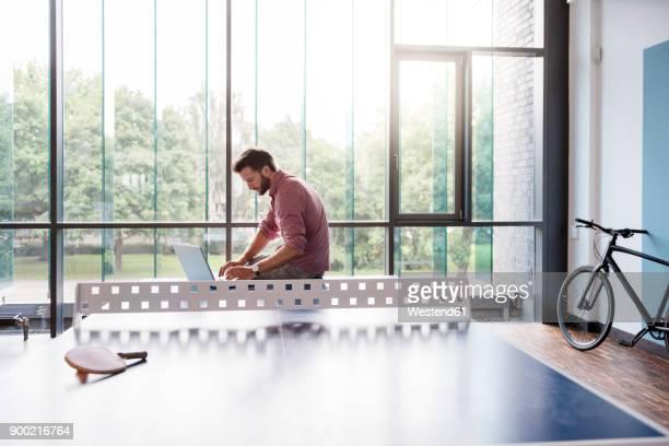 man using laptop in break room of modern office on table tennis table - independência imagens e fotografias de stock