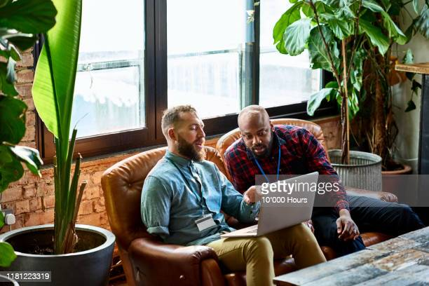 man using laptop in cafe with business colleague - advice stock pictures, royalty-free photos & images