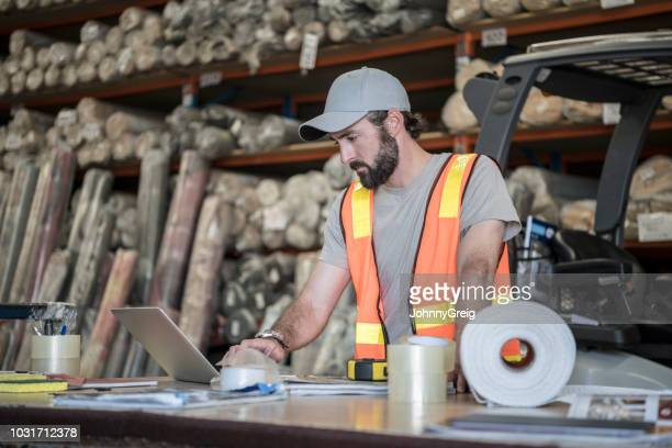 man using laptop in carpet warehouse - mid adult men stock pictures, royalty-free photos & images