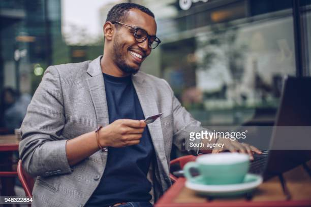 man using laptop in coffee shop - credit card stock pictures, royalty-free photos & images