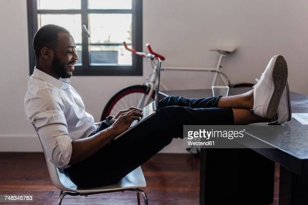 Man using laptop in home office with feet on desk