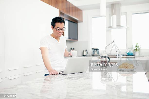 Man using laptop in kitchen