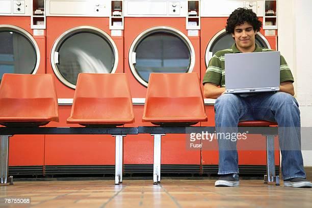 Man Using Laptop in Laundromat
