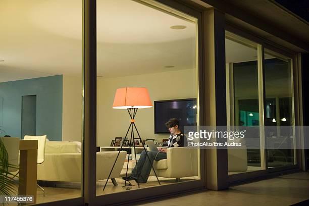 Man using laptop in living room, viewed through window
