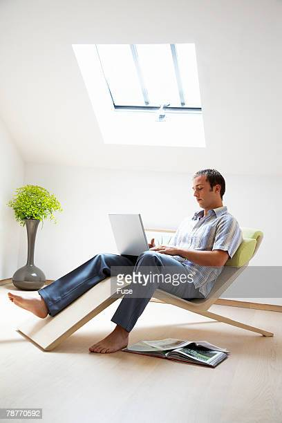 Man Using Laptop in Room with Skylight