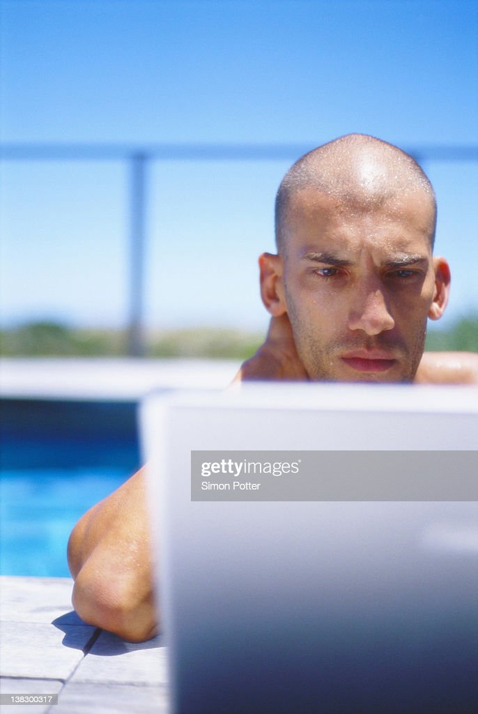 Man using laptop in swimming pool : Stock Photo