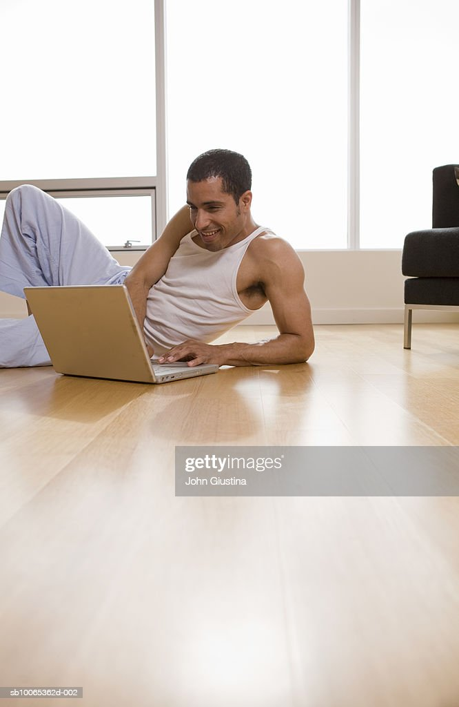 Man using laptop lying floor : Foto stock