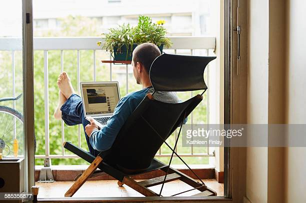 Man using laptop on balcony