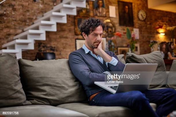 man using laptop on couch at home - western europe stock pictures, royalty-free photos & images