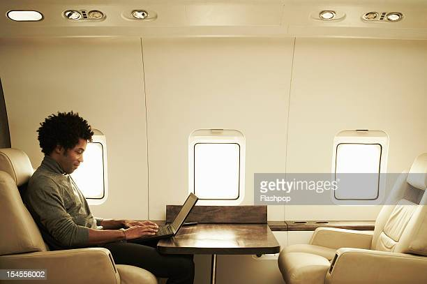 man using laptop on private jet - wireless technology stock pictures, royalty-free photos & images