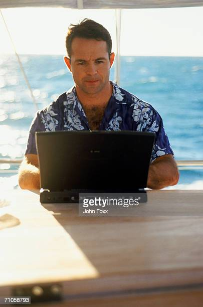 man using laptop on sailboat - mid adult men stock pictures, royalty-free photos & images