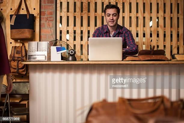 Man using laptop on shop counter