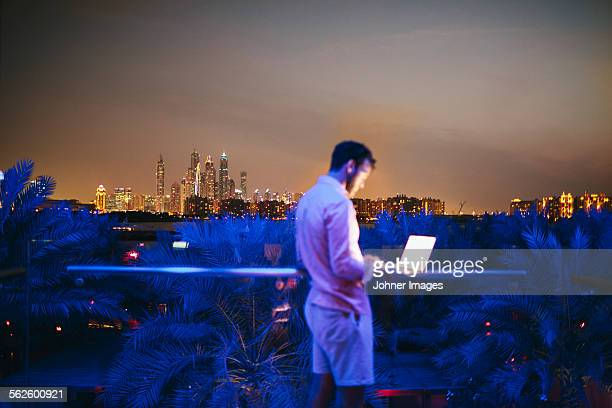 Man using laptop on terrace, cityscape on background