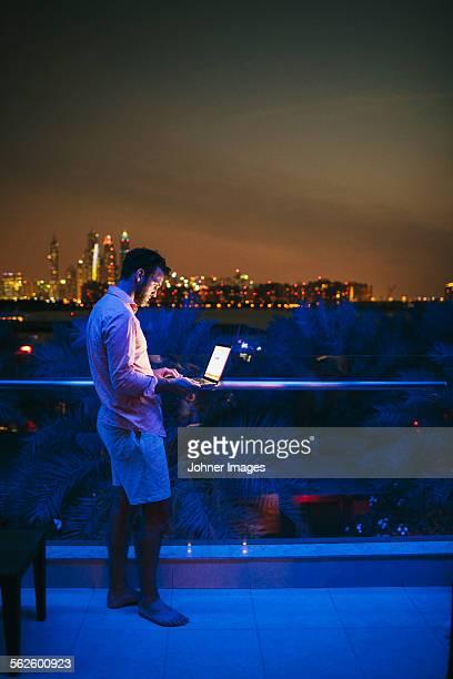 Man using laptop on terrace, cityscape on background