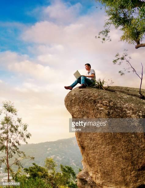 Ein Mann mit Laptop auf dem Felsen