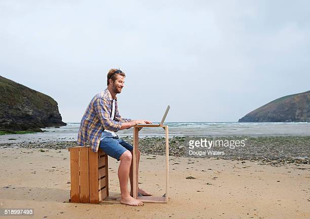 Man using laptop on wooden crate at beach.