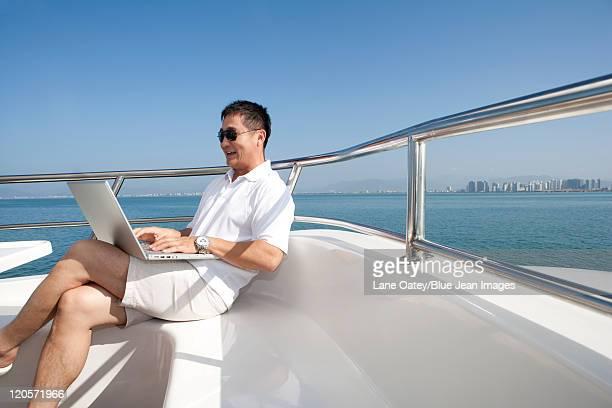 Man Using Laptop on Yacht