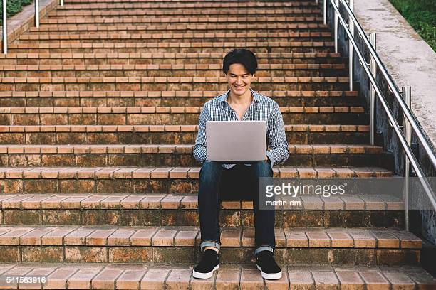 Mann benutzt laptop außerhalb
