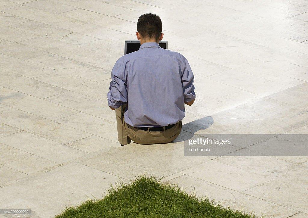 Man using laptop, rear view. : Stockfoto
