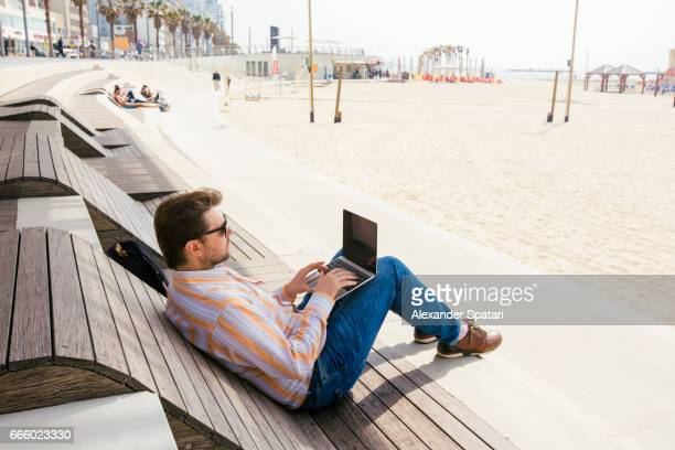 Man using laptop sitting on a wooden sunbed on the beach