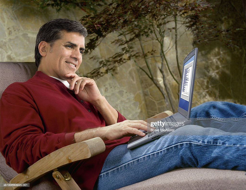 Man using laptop sitting on sunlounger in courtyard : Stockfoto