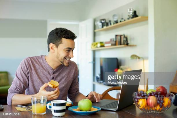 man using laptop while having breakfast at home - one young man only stock pictures, royalty-free photos & images