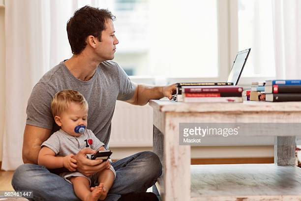 Man using laptop while holding baby boy at home