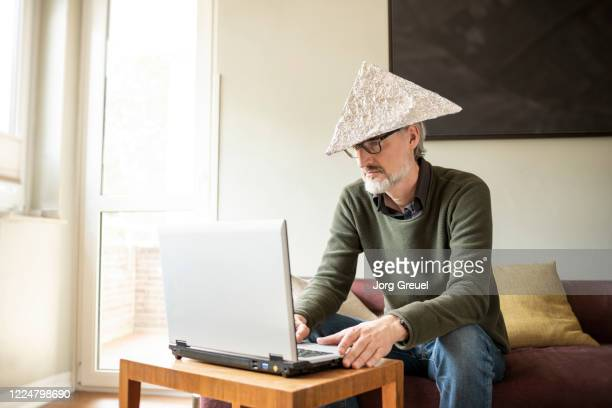 man (age 51) using laptop while wearing a tinfoil hat - aluhut stock-fotos und bilder