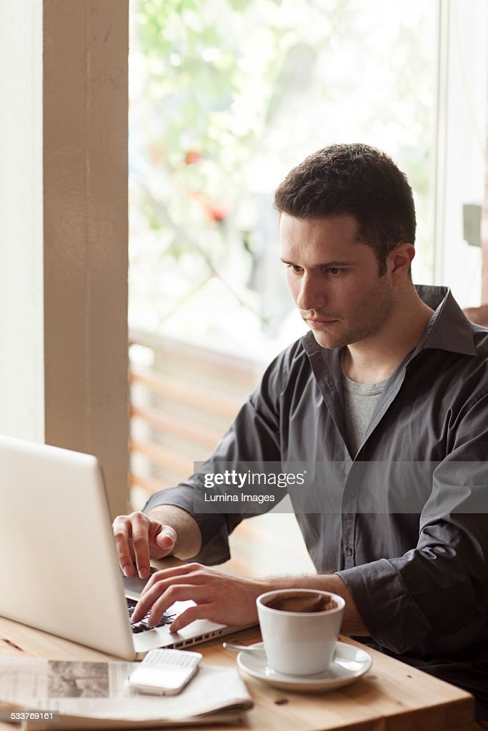 Man using laptop with cup of coffee in cafe : Foto stock