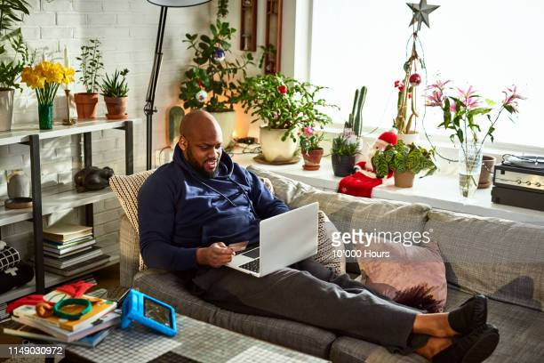 man using laptop with feet up on sofa - home shopping stock pictures, royalty-free photos & images