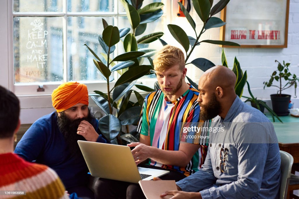 Man using laptop with multi racial colleagues : Stock Photo