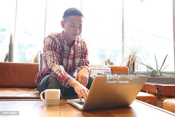 Man using laptop,sitting on sofa in room
