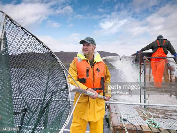 Man using large fishing net in Scottish salmon farm on loch