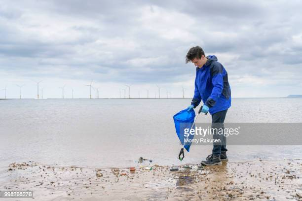 man using litter picker to remove plastic pollution collected on beach, north east england, uk - monty rakusen stock pictures, royalty-free photos & images