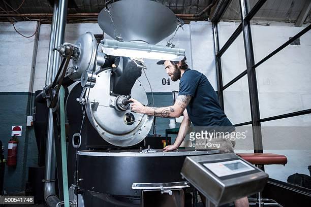Mann mit Maschinen in Kaffee gebratene warehouse