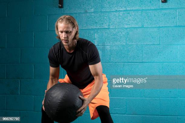 man using medicine ball while exercising against wall in gym - medicine ball stock pictures, royalty-free photos & images