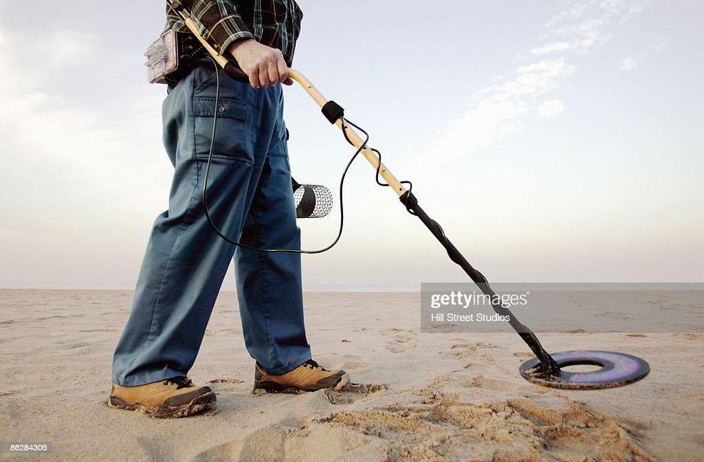 Man using metal detector at beach : Stock Photo