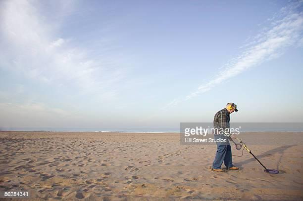 Man using metal detector at beach