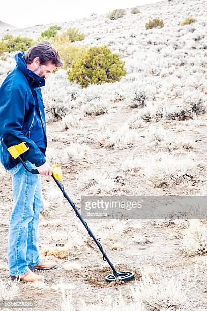 Man using metal detector in Black Rock desert, Nevada, America, USA