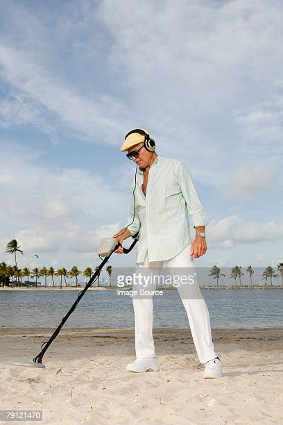 man using metal detector on a beach - metal detector stock photos and pictures