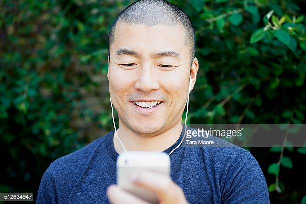 man using mobile and headphones