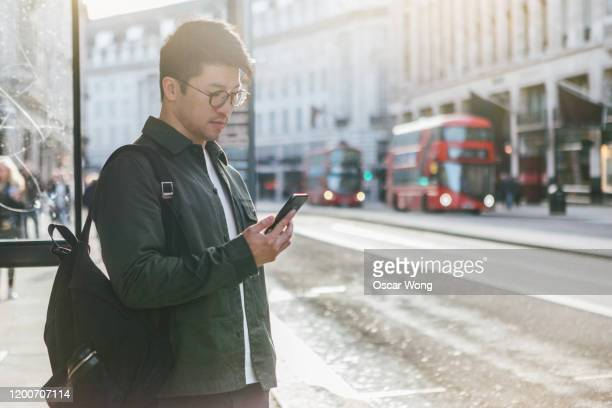a man using mobile app on smartphone to arrange uber ride in city street - mobile app stock pictures, royalty-free photos & images