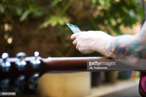 Man using mobile phone across guitar
