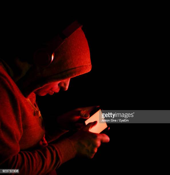 man using mobile phone against black background - hoodie headphones stock pictures, royalty-free photos & images
