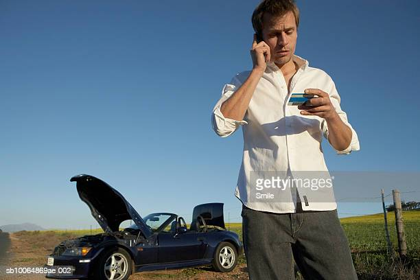 Man using mobile phone and  holding credit card in front of broken down car