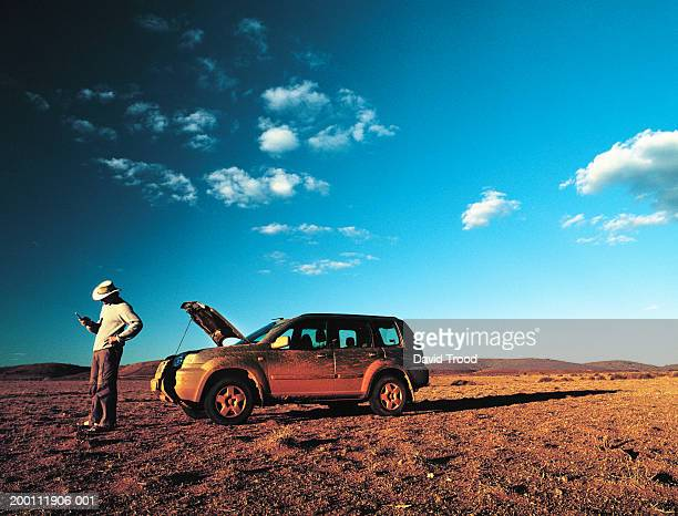 Man using mobile phone beside 4x4 with open bonnet