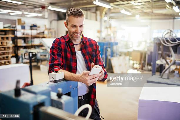 Man using mobile phone in factory