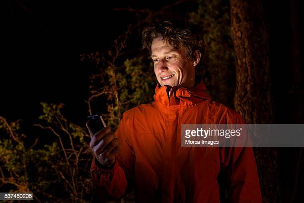 man using mobile phone in forest at night - glowing stock pictures, royalty-free photos & images