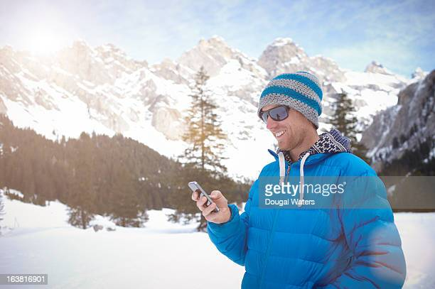Man using mobile phone in mountain snow scene.